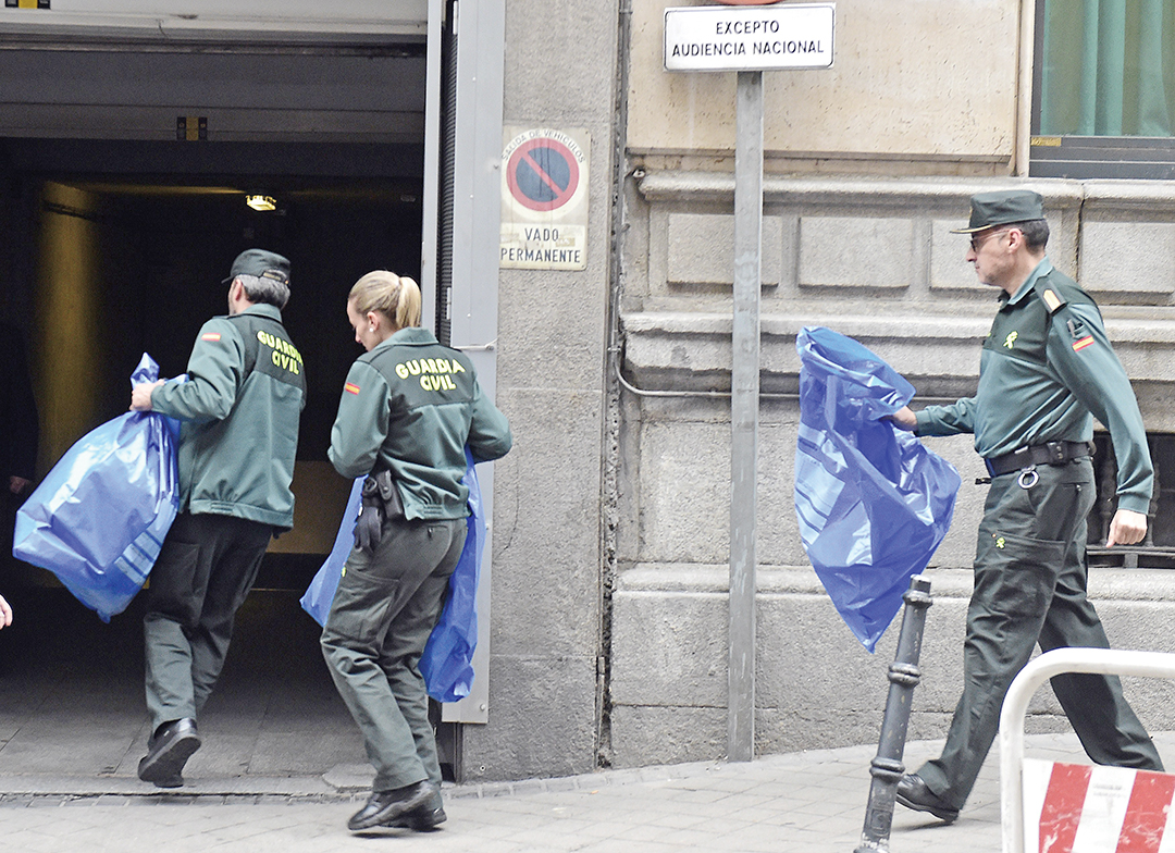 Members of the Spanish Civil Guard carry evidence at the Spanish National Court in Madrid that was seized in the arrest of 10 people in April 2015 in Barcelona and Tarragona. They were accused of trying to travel to Syria and Iraq and are suspected of links to the Islamic State group. AFP/GETTY IMAGES