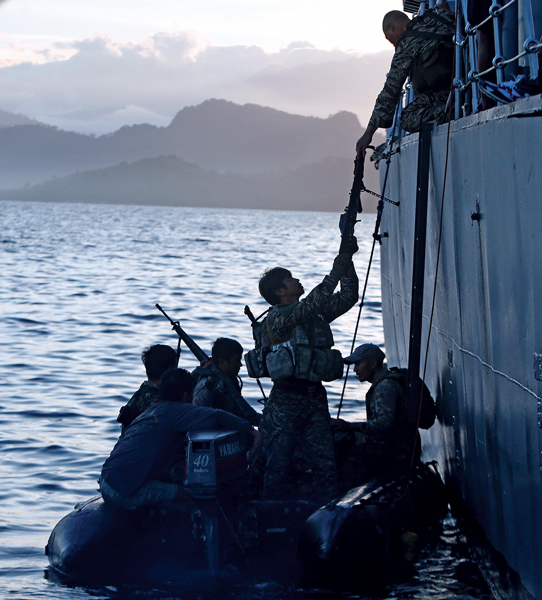 Philippine Marines transfer from a patrol boat to a rubber boat after conducting a mission at the disputed Second Thomas Shoal, part of the Spratly Islands in the South China Sea. They were returning to a naval forces camp in Palawan province, southwest Philippines, in March 2014. REUTERS