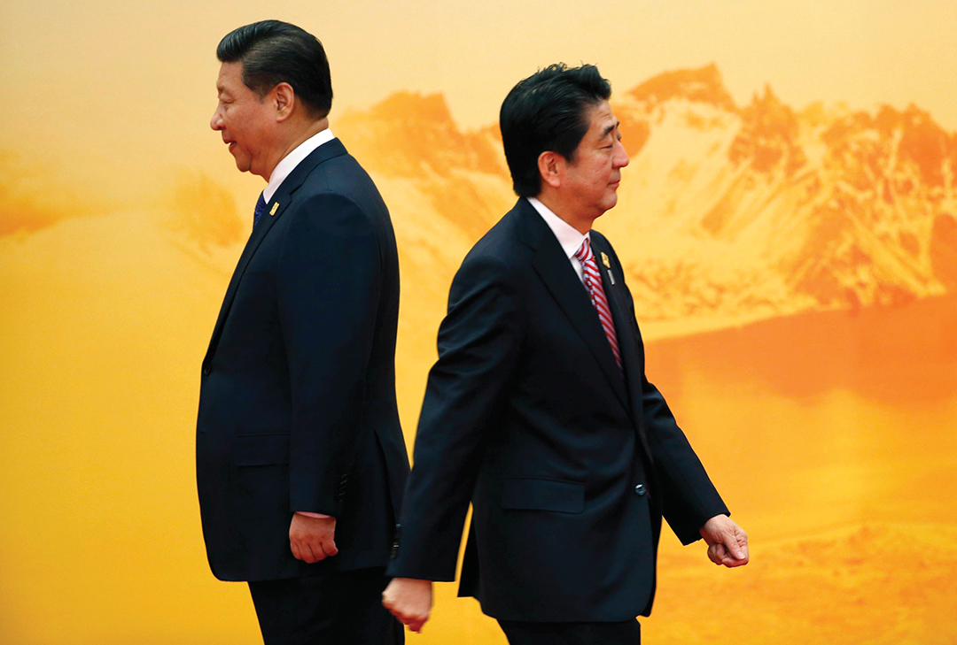 Japan's Prime Minister Shinzo Abe, right, walks past China's President Xi Jinping during a ceremony at the Asia Pacific Economic Cooperation forum in Beijing in November 2014. REUTERS