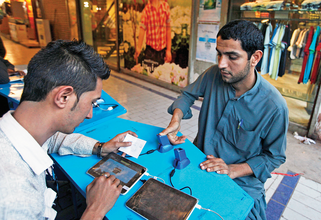A customer scans his thumb for biometric verification on his cellular phone's subscriber identification module at a mobile counter in Karachi, India. REUTERS