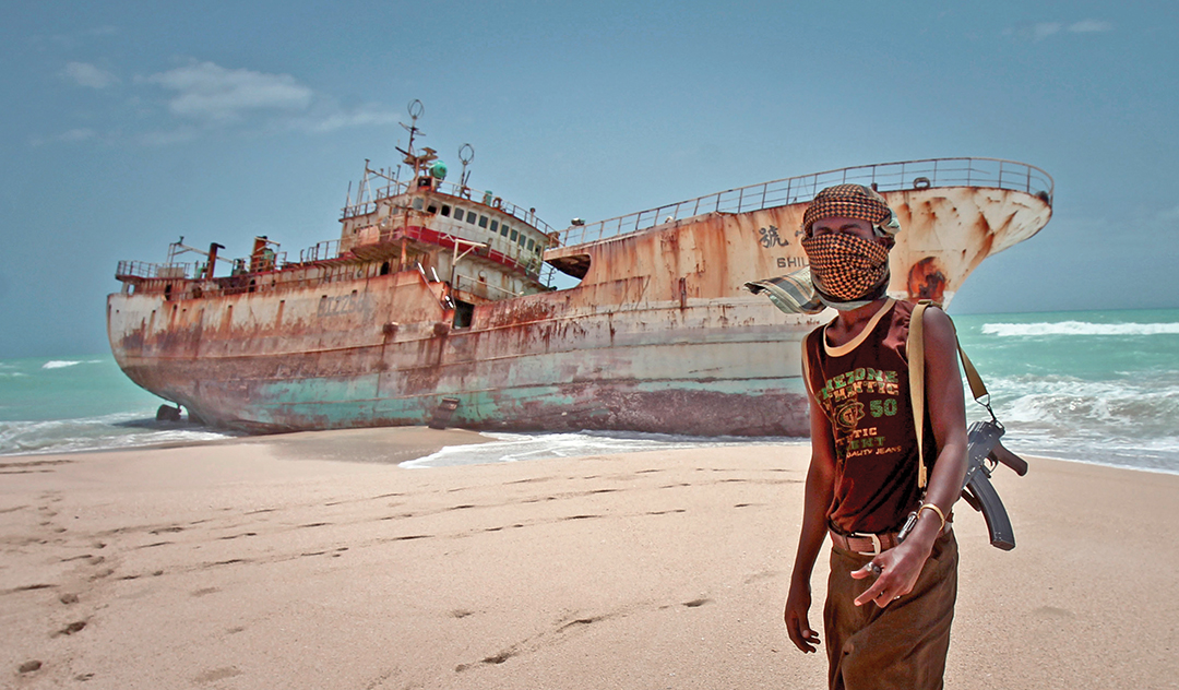 Masked Somali pirate Abdi Ali stands near a Taiwan fishing vessel in September 2013 that washed ashore in Hobyo, Somalia, after pirates were paid a ransom and released the crew. [THE ASSOCIATED PRESS]