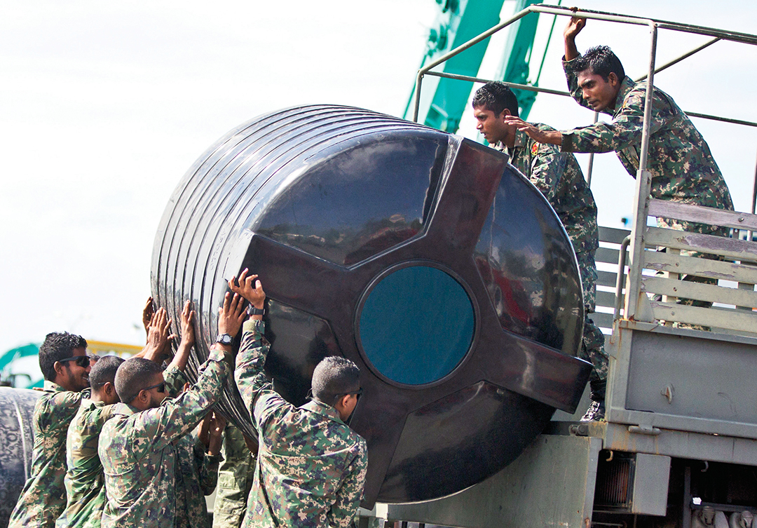 Maldivian Soldiers load a water tank onto a military vehicle in Male in December 2014. The capital, situated on a low-lying island, relies entirely on treated seawater. THE ASSOCIATED PRESS