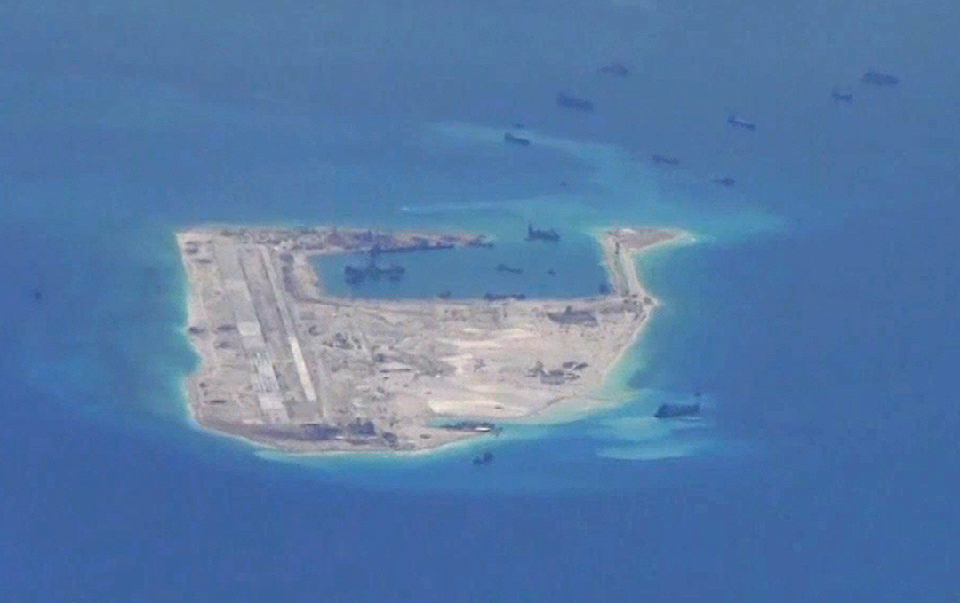 Chinese dredging vessels are purportedly seen in the waters around Mischief Reef in the disputed Spratly Islands in the South China Sea. This image was taken by a U.S. Navy P-8A Poseidon surveillance aircraft in May 2015.