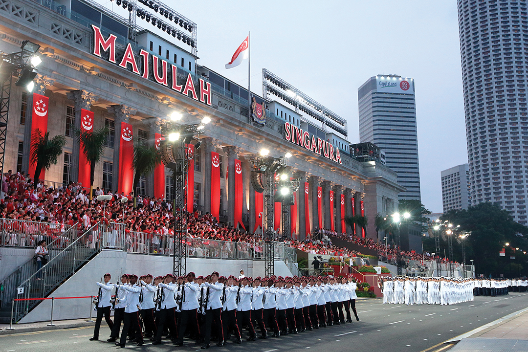 A guard of honor marches past City Hall in August 2015 during the 50th anniversary celebration of Singapore's independence. [Getty Images]