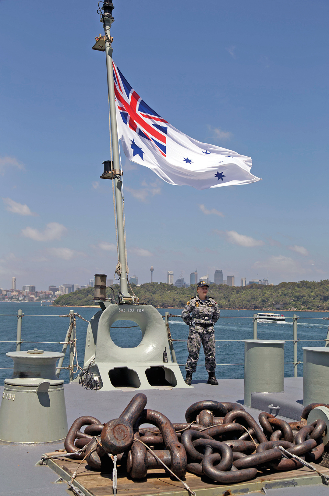A Royal Australian Navy Seaman stands by to lower the flag as HMAS Canberra sails from Sydney Harbor to commence Fleet Concentration Period East 2015.