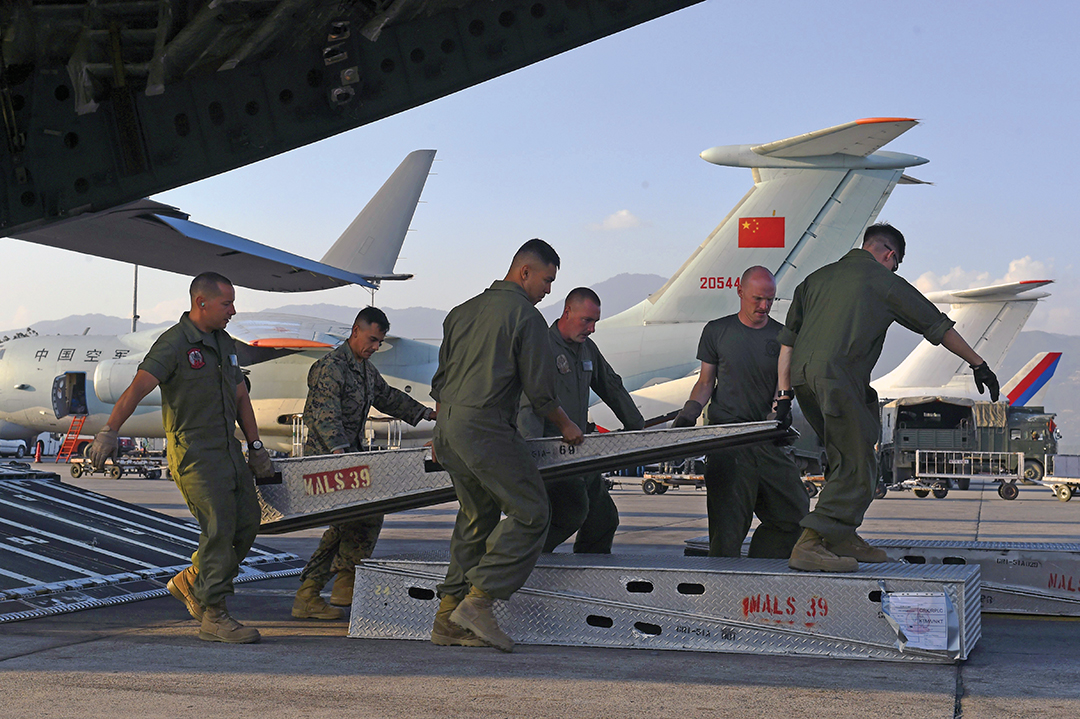 International aid poured into Nepal in the aftermath of two devastating earthquakes in April and May 2015. U.S. crew members from a U.S. C-17 cargo plane prepare to unload a Huey helicopter they transported to Kathmandu's international airport in May 2015. Military transport planes from China and Russia are parked next to the C-17, all part of the multilateral relief effort. AFP/GETTY IMAGES