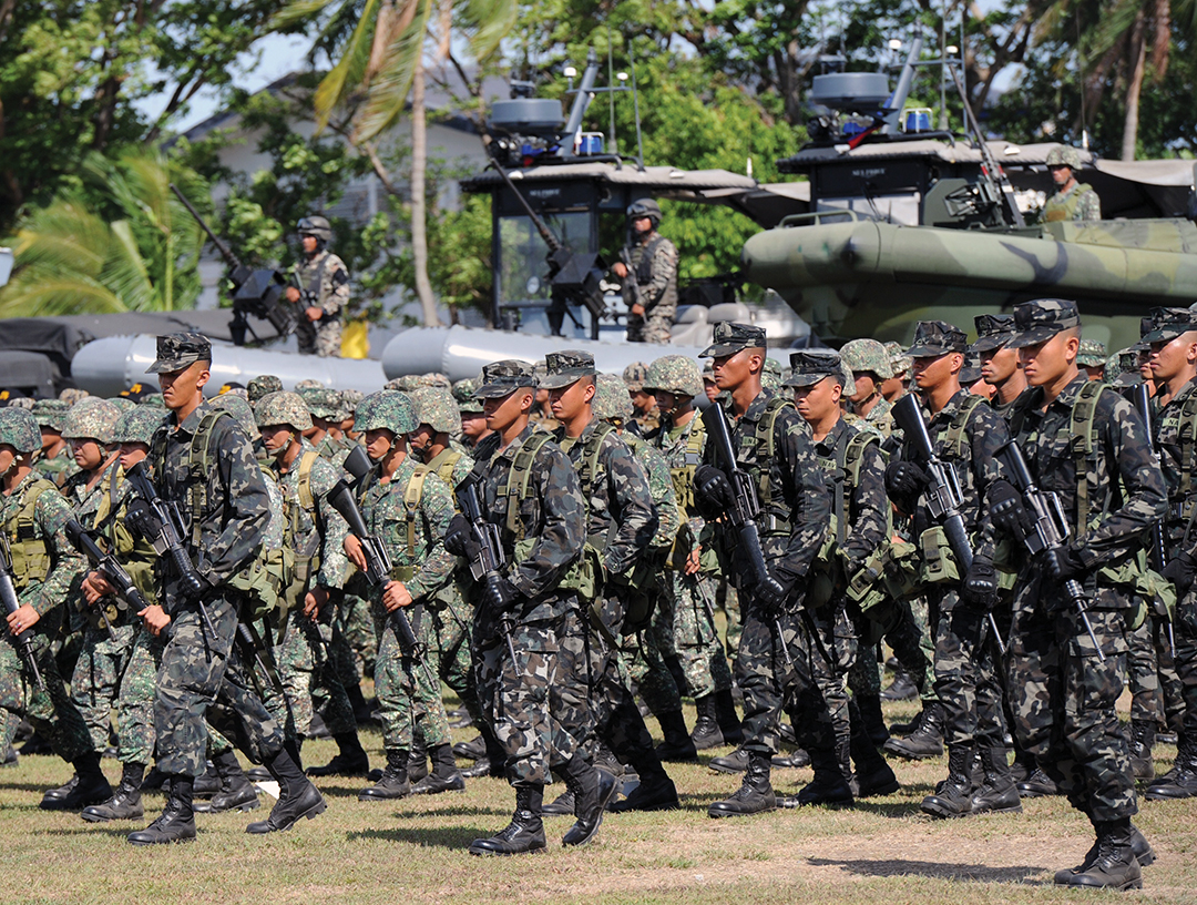 Philippine Marines march next to rigid-hulled inflatable patrol boats during a Navy anniversary celebration in Cavite City in May 2015.