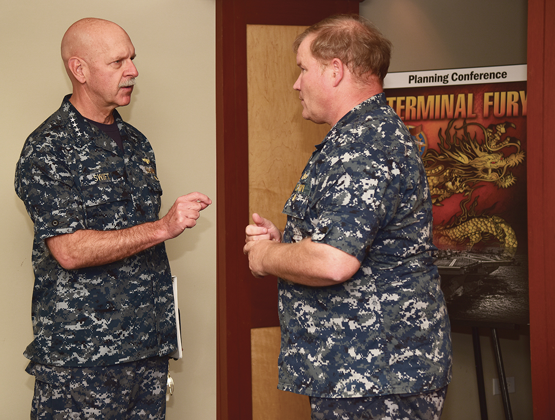 Adm. Scott H. Swift, left, and Rear Adm. Mark C. Montgomery confer during a leaders planning conference.
