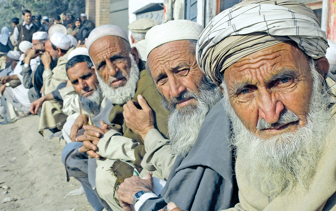 Internally displaced Pakistanis wait for relief goods from the United Nations at a distribution center in Peshawar, Pakistan, in December 2014.