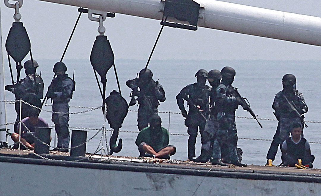 Philippine Coast Guard anti-terror personnel board a cargo vessel to engage mock pirates who hijacked the ship during a combined maritime law enforcement exercise with Japan in a Manila bay in May 2015. REUTERS