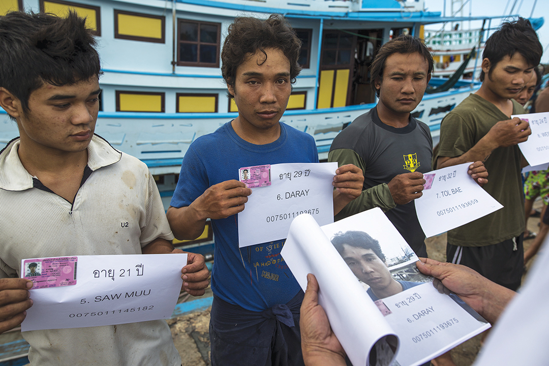 Migrant workers hold up their identity cards as authorities conduct a check at a port in Samut Songkhram province, Thailand, in July 2015. Reuters