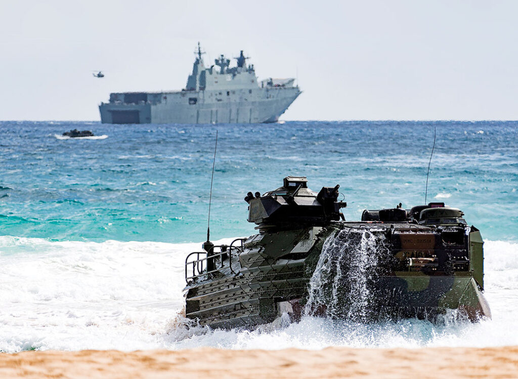 A U.S. Marine Corps amphibious assault vehicle hits the beach after disembarking from the Royal Australian Navy's amphibious ship HMAS Adelaide during the 2018 Rim of the Pacific exercise.