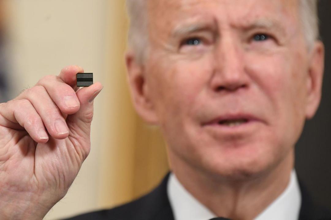 重要なサプライチェーンの確保を目的とした大統領令に署名する前に、マイクロチップを掲げて見せるジョー・バイデン米大統(AFP/GETTY IMAGES)