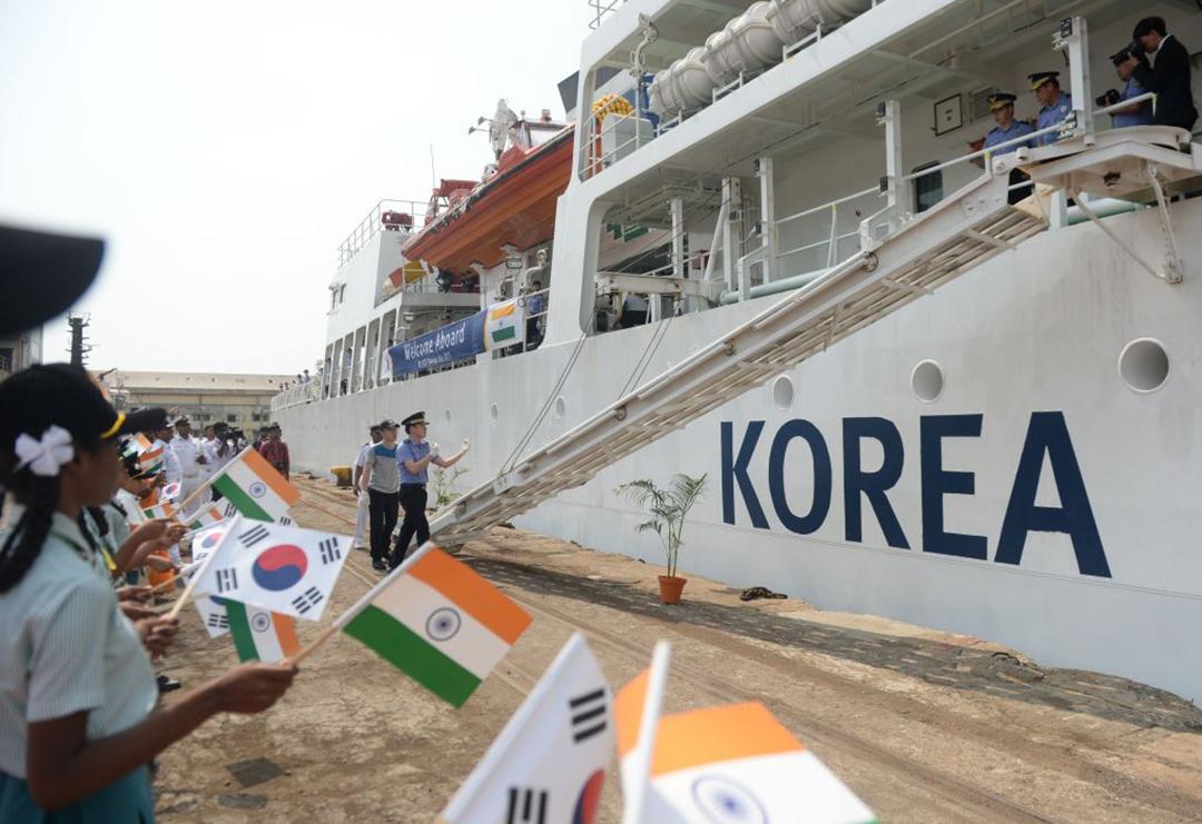 インド沿岸警備隊[ICG]との合同演習のためにインドのチェンナイに到着した韓国海洋警察庁[KCG]の訓練船「バダロ(BADARO)」を両国の国旗を振って迎えるインド人学生等(AFP/GETTY IMAGES)