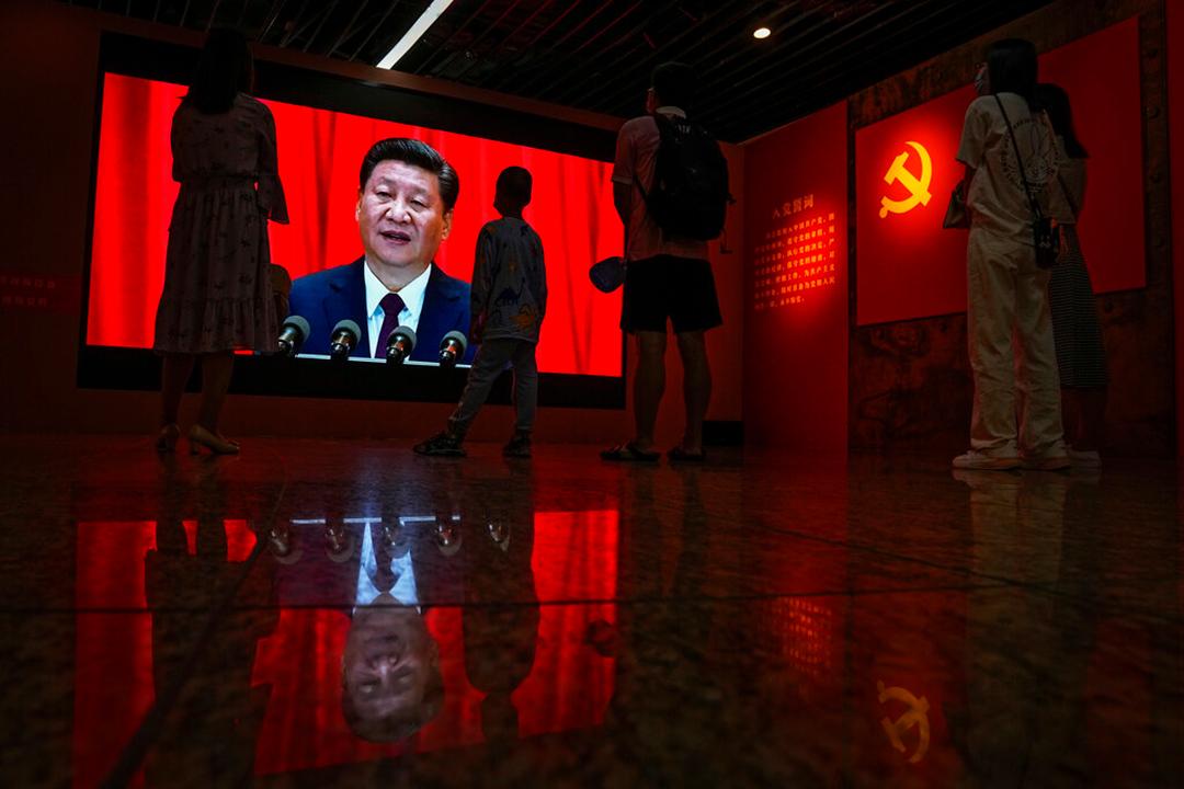 1921年以来、中国共産党指導下で中国が築いてきた功績を宣伝する展示会で習近平主席が映し出された画面を見る来館者等(AP通信社)