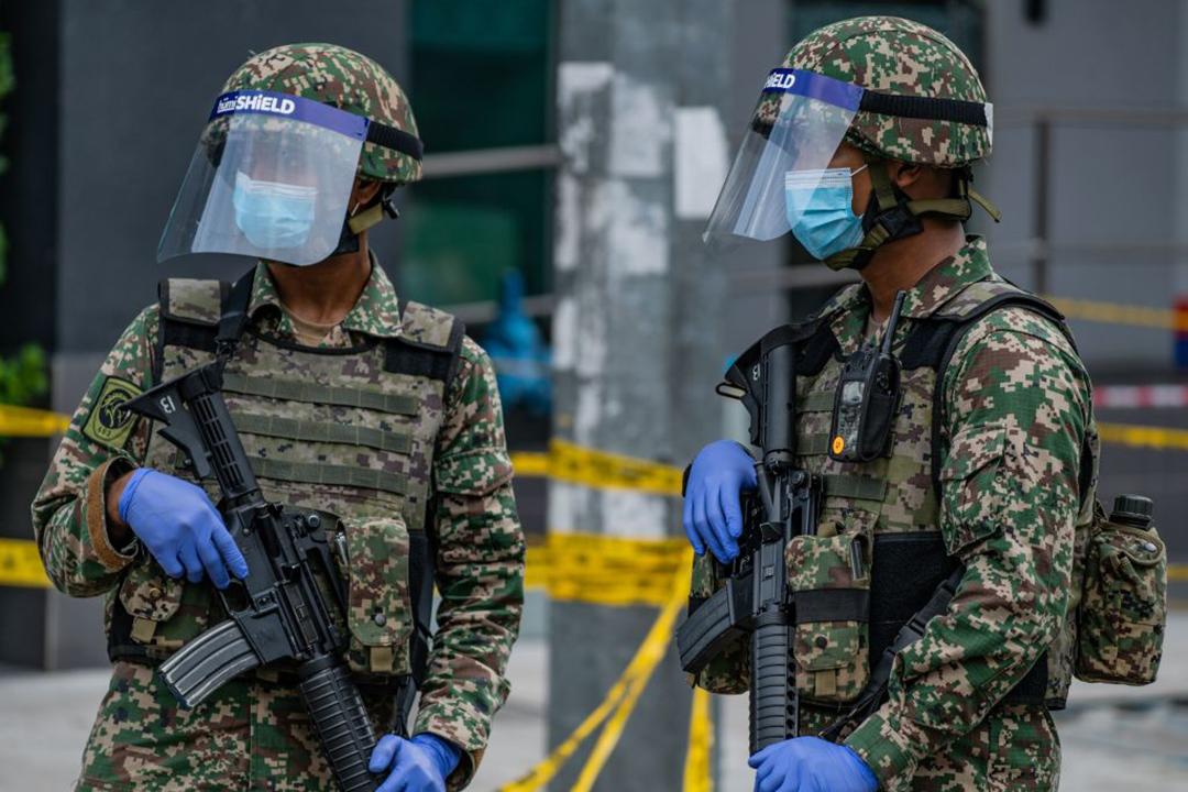新型コロナウイルス感染症パンデミック対策として封鎖されたクアラルンプールの市場を警備するマレーシア軍兵士等(AFP/GETTY IMAGES)