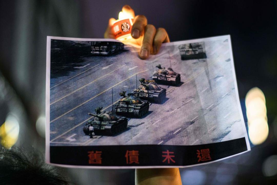 (写真:2020年6月4日、六四天安門事件の犠牲者を追悼することを目的として香港で開催されたキャンドルビジルで、1989年6月に天安門広場に通ずる路上で中国人民解放軍の戦車の行く手を阻む男性[氏名不詳のために「戦車男」や「無名の反逆者」と呼ばれている]の写真を掲げる男性)