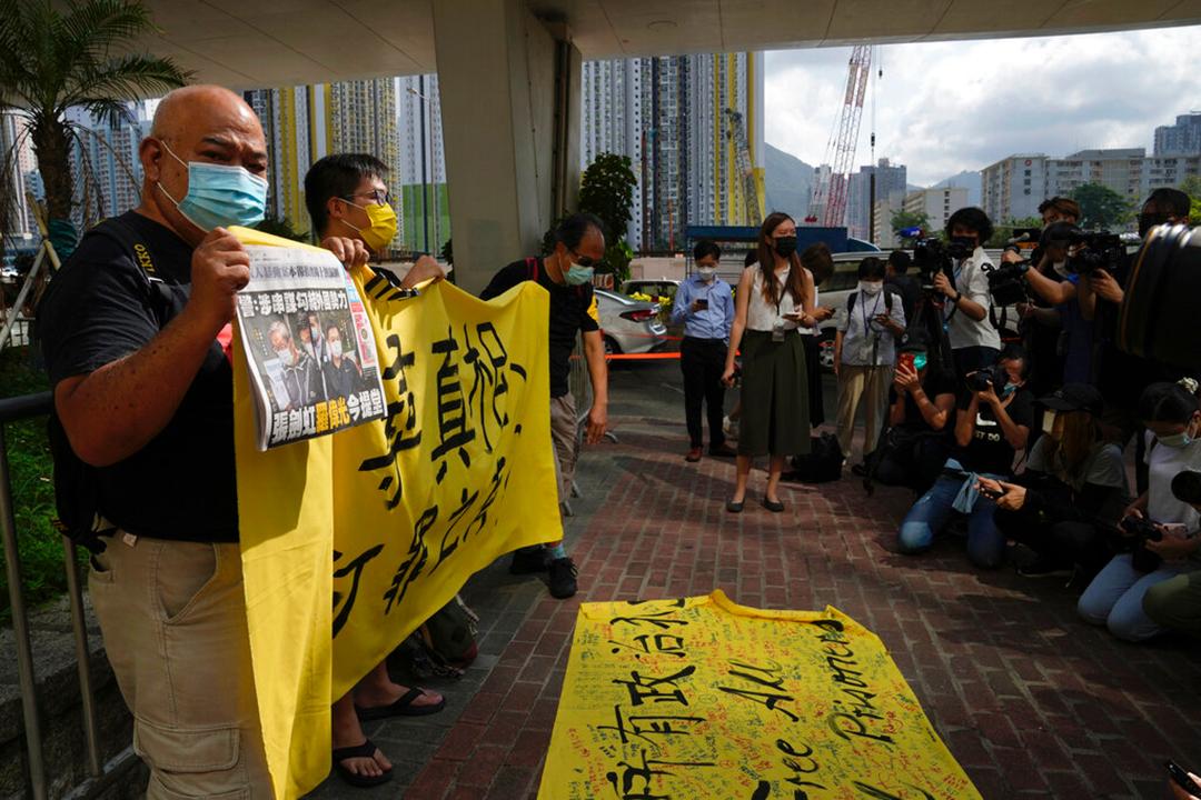 2021年6月19日、香港裁判所前で蘋果日報の新聞と横断幕を掲げて政治犯の釈放を要求する民主派抗議者等