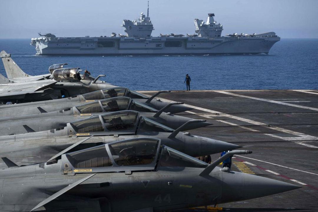 2021年6月3日にフランス沖で実施された演習で、フランス海軍空母「シャルル・ド・ゴール(Charles de Gaulle)」に搭載されたフランス空軍のラファール戦闘機。背景はクイーン・エリザベス空母(AFP/GETTY IMAGES)