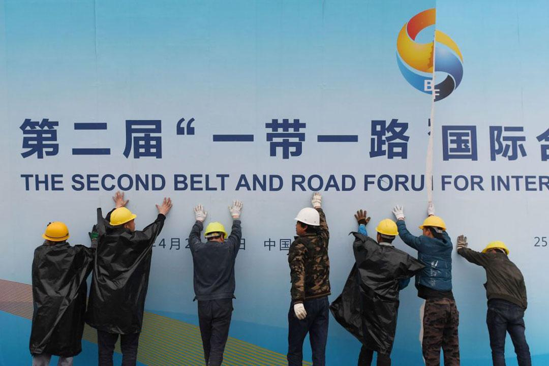 2019年4月、北京の会場の外で一帯一路フォーラムパネルを取り外す労働者等(AFP/GETTY IMAGES)