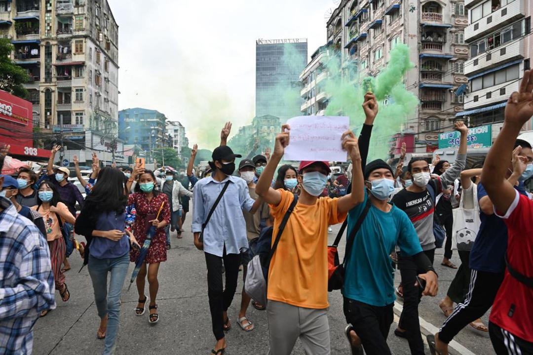 抵抗を表す3本指の敬礼でビルマ軍事クーデターへの反対を示す抗議者等(AFP/Getty Images)