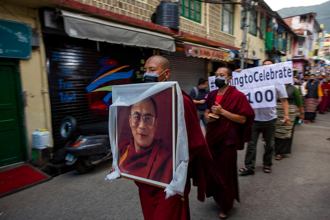 2021年7月、インドのダルムサラで中国共産党の創立100周年に反対する抗議活動においてチベットの精神的指導者であるダライ・ラマの肖像を掲げる亡命チベット人僧侶(AP通信社)