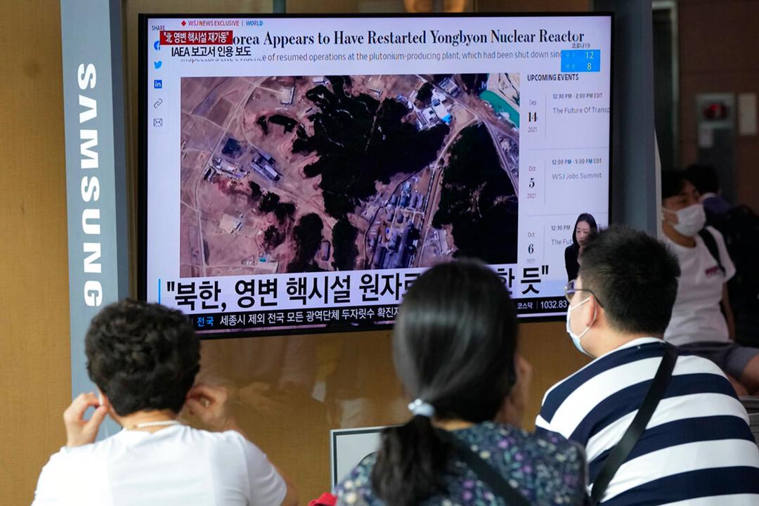 2021年8月30日に北朝鮮の寧辺核施設の衛星画像を表示するテレビを視聴する韓国ソウルの人々。最新の衛星画像によると、北朝鮮は工場での兵器用燃料の生産を再開し施設のウラン濃縮事業も拡大している(AP通信社)