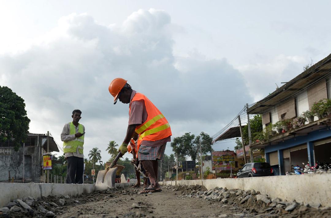 中国の融資で資金調達されたスリランカのコロンボの道路を建設する労働者(AFP/Getty Images)